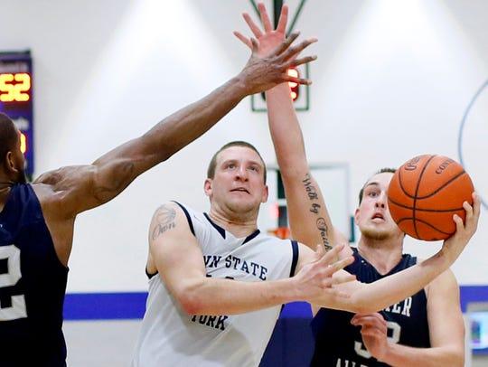 Penn State York's Trent Thomas, center, takes the ball