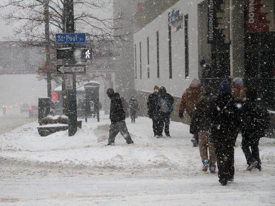 Pedestrians walk on Main Street during a snow storm on February 5, 2014.