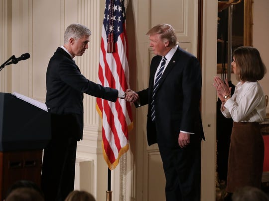President Trump shakes hands with Neil Gorsuch, accompanied