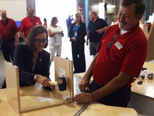 Gov. Kate Brown helps piece together a cabinet box at the Cabinotch Innovative Solutions grand opening ceremony on Thursday, Aug. 10, 2017.