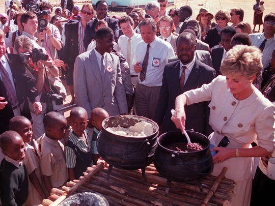 Children wait in line as Diana lends a hand to serve the food at the Child Feeding Scheme at Nemazuva Primary School in Zimbabwe on July 12, 1993. She was on of the first to realize that celebrities could use their influence to bring about change.