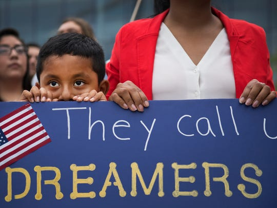Esvin Sosa, 7, stands with his mom at a vigil for Dreamers