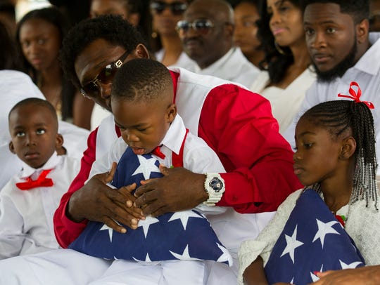 La David Johnson Jr., 2, is presented with an American