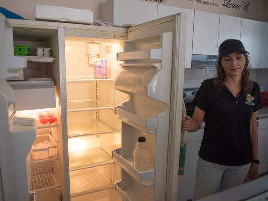 Michelle Rebollo opens her empty refrigerator, her. family has been without power and running water for the past seven weeks. The power returned briefly, but has been intermittent.