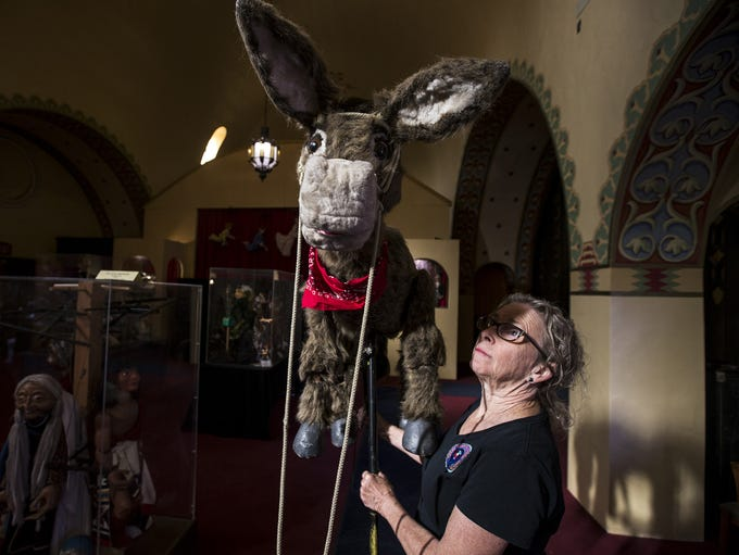 Nancy Smith poses for a portrait with a donkey marionette