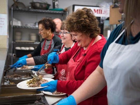 Volunteer Judy McBrearty makes a plate for a guest during Thanksgiving day meal at The Salvation Army in Greenville on Thursday, November 23, 2017.