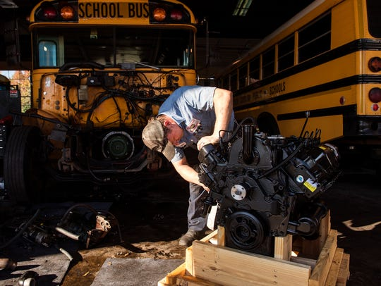 Daniel Gillette unwraps a new bus engine before he