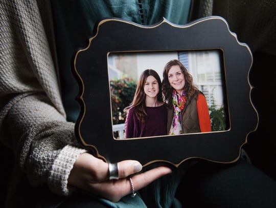 Bladen Bates holds a photograph of her and her sister,
