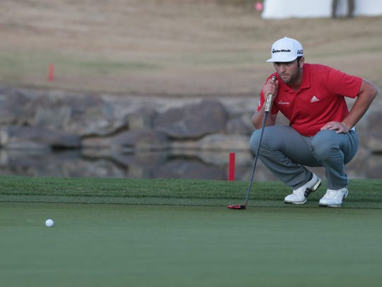 Jon Rahm prepares for a putt during a playoff at the