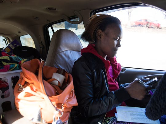 Staneice Hunter sits in her car outside of the Economy Inn and tries to find housing for her and her five kids on Thursday, January 25, 2018.