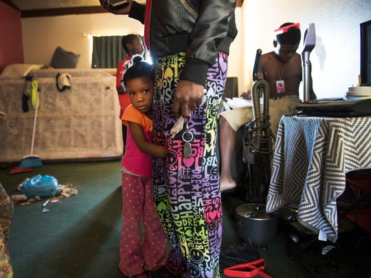 Shaniyha Hunter, 4, hugs her mom's leg in their room they have been living in at the Economy Inn on Thursday, January 25, 2018.