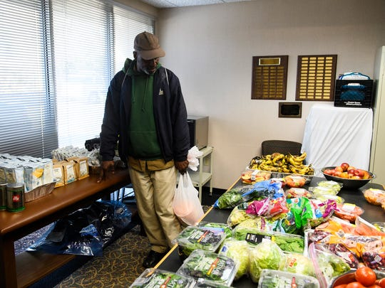 Jimmy Booker looks at produce available at the free