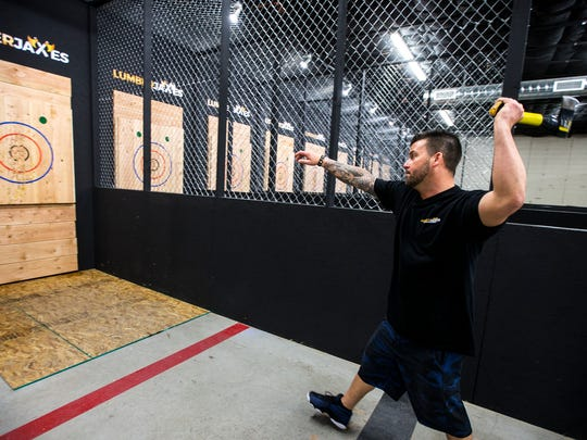 There are several ways to throw an ax. LumberjAxes co-owner Francesco DiNardo demonstrates a one-handed throw at LumberjAxes in Tempe on Feb. 8, 2018.