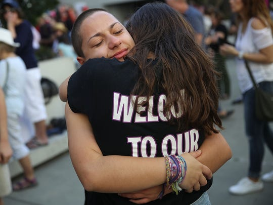 Emma Gonzalez is hugged as she joins other people to protest against guns on the steps of the Broward County Federal courthouse  in Fort Lauderdale.