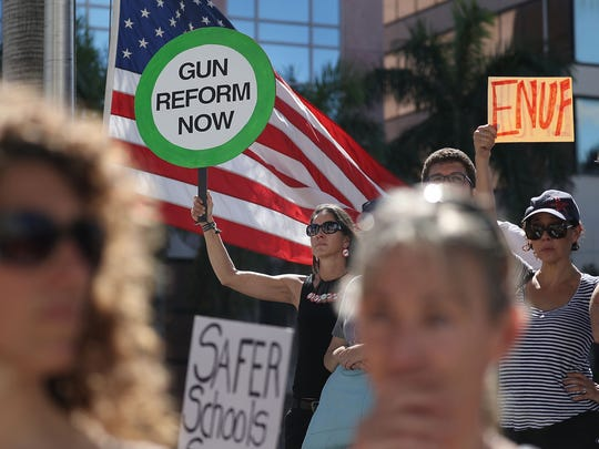 Alessandra Mondolfi holds a sign that reads, 'gun reform now' on the steps of the Broward County Federal courthouse.