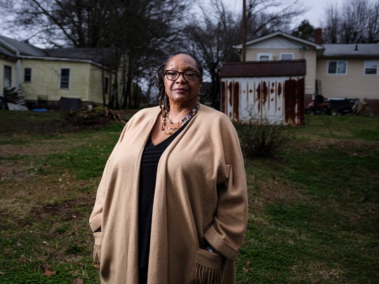 "Joanne Hills, 61, stands between where her mother, Dorothy Jones, and her aunt, Ann Warren, live. The home behind her was her grandmother's, and Hills says she has many memories of growing up there. Hills hopes to move into the neighborhood one day. ""We need to keep properties in the hands of the people who care about them and not in the hands of a developer,"" Hills says."