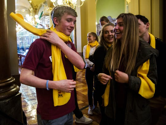 Ben Freking, a student at Dowling Catholic High School throws a yellow national school choice scarf over his shoulder during a rally to support school choice on Wednesday, April 4, 2018 in the rotunda of the Iowa Capitol. Iowa Alliance for Choice in Education hosted the rally to advocate for expanding educational choice throughout Iowa.