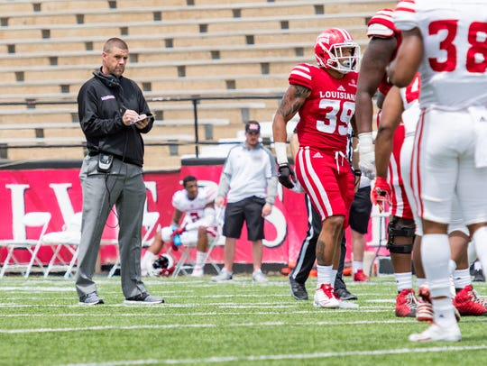 Billy Napier takes notes during his first spring game as coach of the Ragin' Cajuns.
