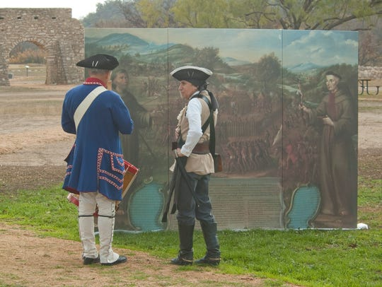 Re-enactors look at a mural in this undated photo at