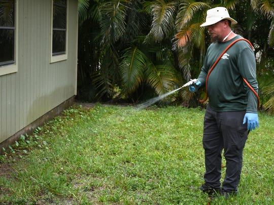 Leon Humphrey of Stahlman Landscaping & Property Maintenance sprays a property for millipedes. Many homes in Collier County have been overrun with a host of yellow banded millipedes.