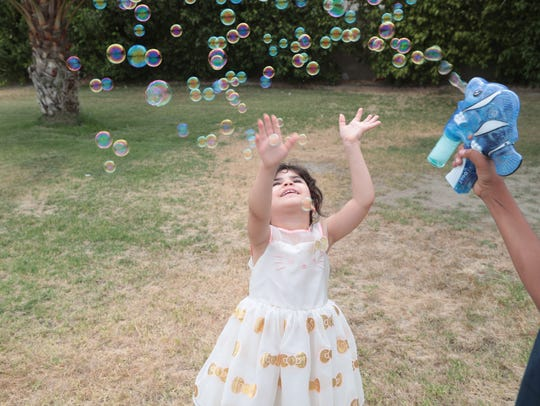 Kids play with bubbles at the Eid al Fitr celebration