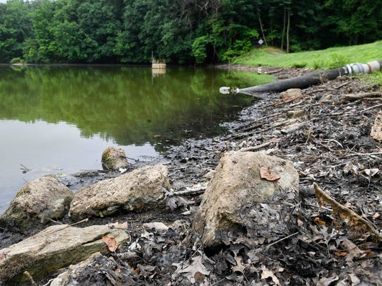 Some of the lake bottom has been exposed as the water level at John James Audubon State Park's main lake has been lowered a couple of feet for the $2 million dam rehabilitation project.