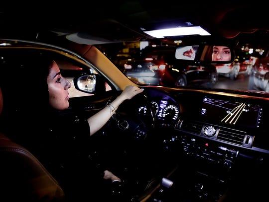 Hessah al-Ajaji drivers her car down the capital's busy Tahlia Street after midnight for the first time in Riyadh, Saudi Arabia, Sunday, June 24, 2018.
