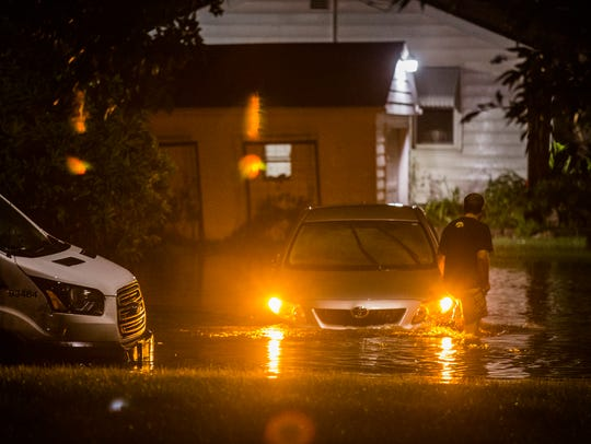 A man wades through flood water to check on a car stalled