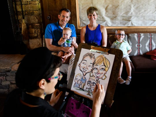 Jason and Lindsey Reekie have a caricature made of them and their children Spencer, 8, and James, 3 months at The Cliffs on Tuesday on, July 3, 2018.