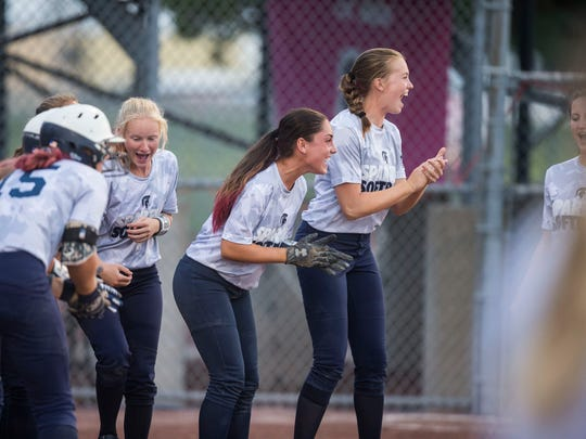 Pleasant Valley players celebrate a teammate scoring a home run during the state softball semifinal between West Des Moines Valley and Pleasant Valley on Wednesday, July 18, 2018, at the Rogers Sports Complex in Fort Dodge.