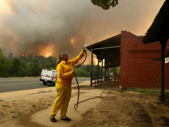 A woman hoses down a building as the Carr Fire burns in the background, on July, 26, 2018, in Whiskeytown, Calif. California Gov. Jerry Brown has declared states of emergency in Riverside and Shasta counties as fires burn on both ends of the state.
