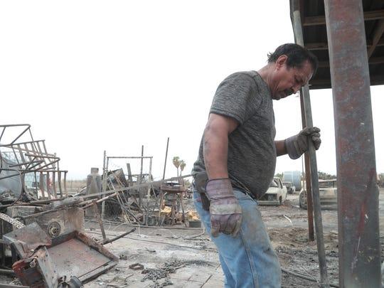 Natividad Armijo works on rebuilding his burned home