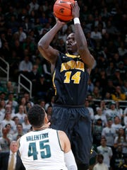 Iowa's Peter Jok (14) shoots over Michigan State's