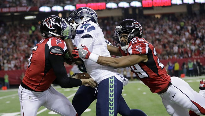 Atlanta Falcons punter Matt Bosher (5) and cornerback C.J. Goodwin (29) tackle Seattle Seahawks wide receiver Devin Hester (17) during a punt return during the first half of an NFL football divisional football game, Saturday, Jan. 14, 2017.