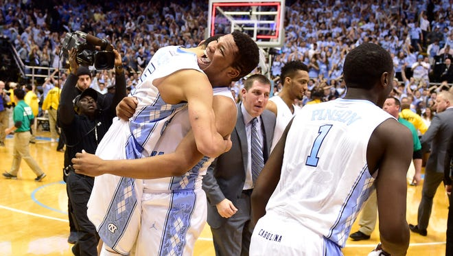 Jan 10, 2015; Chapel Hill, NC, USA; North Carolina Tar Heels guard/forward Theo Pinson (1) and guard Marcus Paige (5) and forward Kennedy Meeks (3) react after the game. The Tar Heels defeated the Cardinals 72-71 at Dean E. Smith Center. Mandatory Credit: Bob Donnan-USA TODAY Sports
