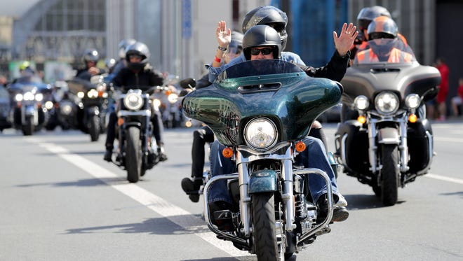 Harley riders wave as they head through the streets of Prague during the parade.