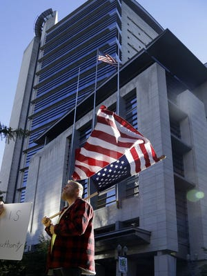 A protester flies an upside down American flag outside the federal courthouse in Portland, Ore., Tuesday, Sept. 13, 2016. (AP Photo/Don Ryan)