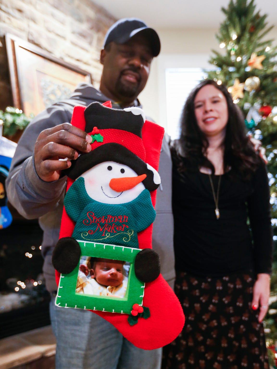 Elizabeth and Eric Washington hold the stocking for
