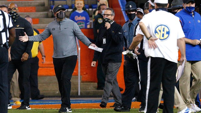 Missouri coach Eli Drinkwitz gestures toward Florida coach Dan Mullen, obscured at right, after a fight broke out at the end of the first half during a game Saturday night in Gainesville, Fla.