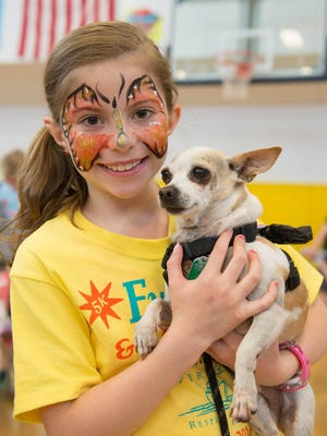 Leah Meade, 9, of Shelburne holds her dog Bailey before the start of the VNA Vermont Respite House 5K Fun Run & Jiggety Jog in Williston on Saturday.