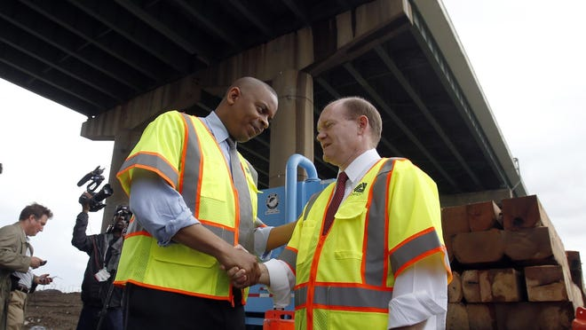 Department of Transportation Secretary Anthony Foxx (left) greets US Senator Chris Coons under the I-495 bridge Friday. Foxx said the $20 million for repairs will be covered by federal funds.