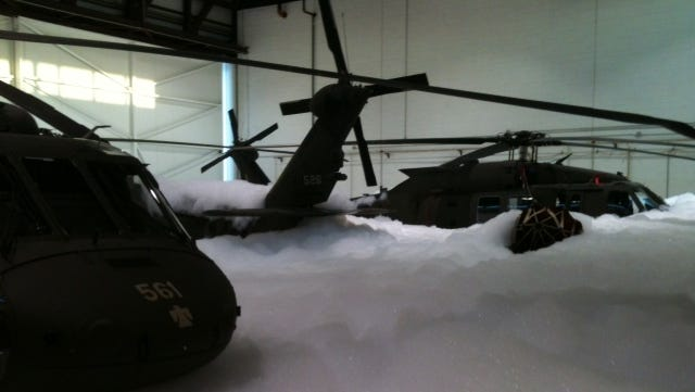 Helicopters covered in fire-suppression foam at the Oklahoma Army National Guard aviation facility in Tulsa.