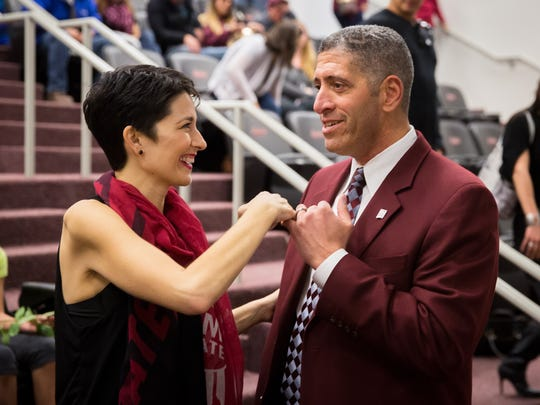 """NMSU Honorary Team Captain Lori Paulson makes a """"pinky swear"""" with Aggie Athletic Director Mario Moccia at the Hall of Legends on Thursday. NMSU hosted a reception in January at the Hall of Legends to name the football team meeting room after Paulson, who is battling pancreatic cancer, recognizing her efforts as honorary captain and her family's donation of $100,000 to the NMSU football program."""