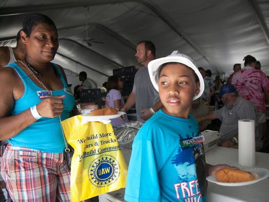 Lolee Jones and her son Eric Jett, age 9, pass through the lunch buffet during the Greater Louisville United Labor Picnic held at the Louisville Zoo.  Sept., 1, 2014