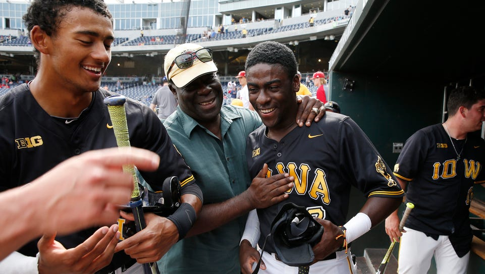 Iowa outfielder Devin Pickett is hugged by former administrator