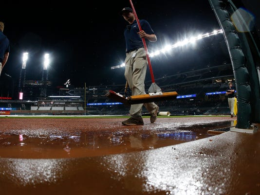 A member of the Atlanta Braves grounds crew walks past the visitor's dugout as rain falls during a rain delay in a scheduled baseball game between the Atlanta Braves and Texas Rangers, Tuesday, Sept. 5, 2017, in Atlanta. (AP Photo/John Bazemore)