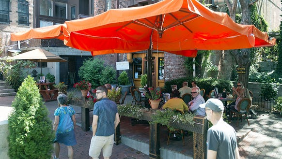 Diners crowd the patio on a warm, late-summer day at