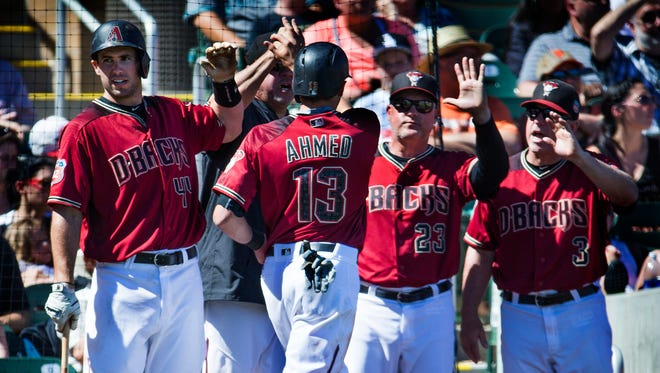 Arizona Diamondbacks shortstop Nick Ahmed is congratulated after scoring a run against the San Francisco Giants during the third inning at Salt River Fields at Talking Stick, Wednesday, March 23, 2016. From left are; Paul Goldschmidt, Ahmed, pitching coach Mike Butcher, and manager Chip Hale.