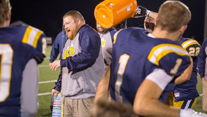 The team dumps a cooler of Gatorade on Delta head coach Christopher Overholt after the win against Mt. Vernon in the sectional game Friday night at Delta High School.