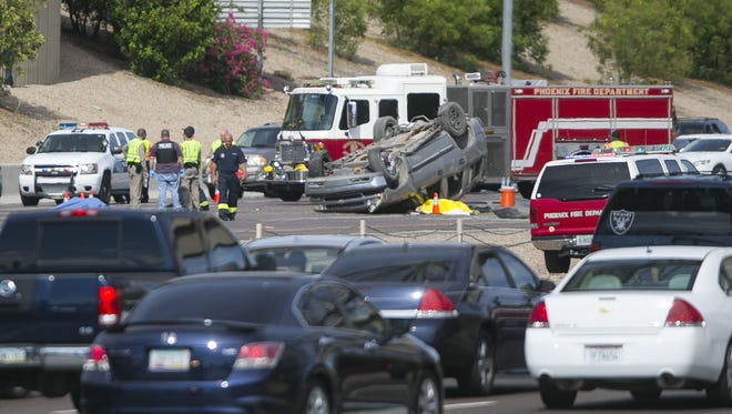 An overturned car is seen Sunday afternoon after a crash on the Interstate 10 in Phoenix on Sunday, July 25, 2015.